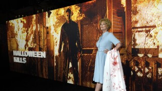 Jamie Lee Curtis poses next to backdrop of 'Halloween Kills' while dressed as Marion Crane at Hollywood premiere in 2021