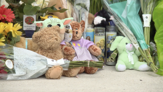 closeup of mementos left at memorial outside Royal Palm Beach Publix where child and grandmother were killed