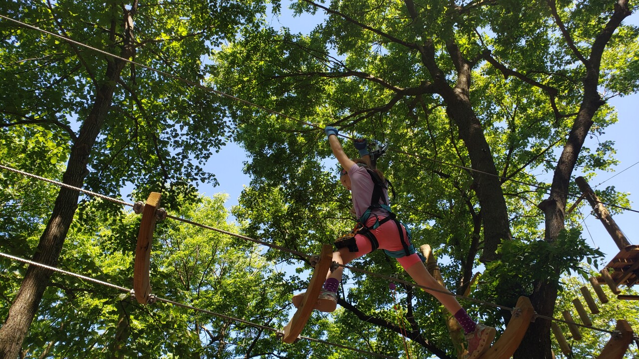 A young woman attempts to navigate an obstacle course at TreeRush Adventures