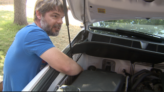 Jefferson Patrick shows where squirrels feasted on his car's wiring