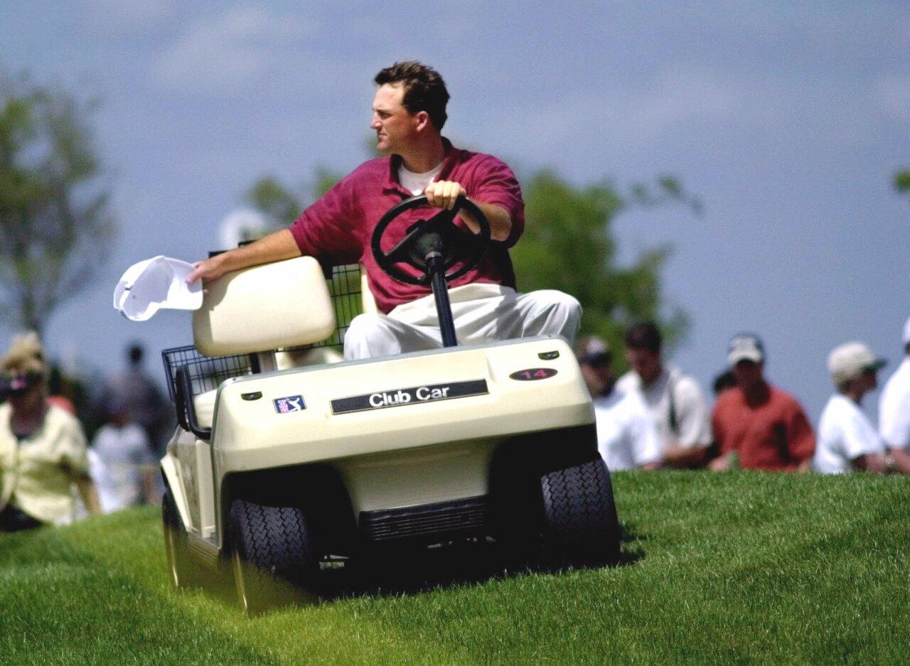 Casey Martin followed by fans on golf cart at 2000 Honda Classic