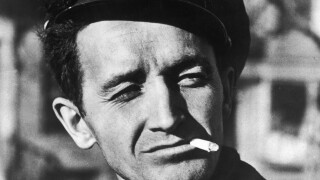 Headshot of American singer and musician Woody Guthrie (1912 - 1967) smoking a cigarette and squinting outdoors, c. 1960. He wears a fishing cap, turtleneck sweater, and a peacoat. (Photo by Getty Images)