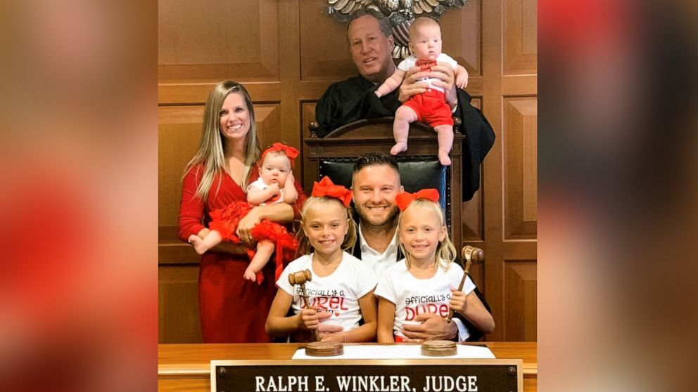 BJ Durel, seated, and Calena Durel, far left, celebrate the adoption of Maria and Aubree, seated.