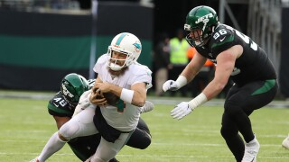 Ryan Fitzpatrick #14 of the Miami Dolphinsdives for yardage as he is tackled by Jordan Jenkins #48 of the New York Jets during their game at MetLife Stadium on December 08, 2019 in East Rutherford, New Jersey.
