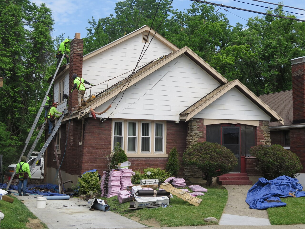 A crew from Deer Park Roofing works to install a new roof on Naima Jackson's home on May 24, 2021. Ladders are extended so crews can reach two levels of roofing, and materials are stacked in Jackson's front yard.