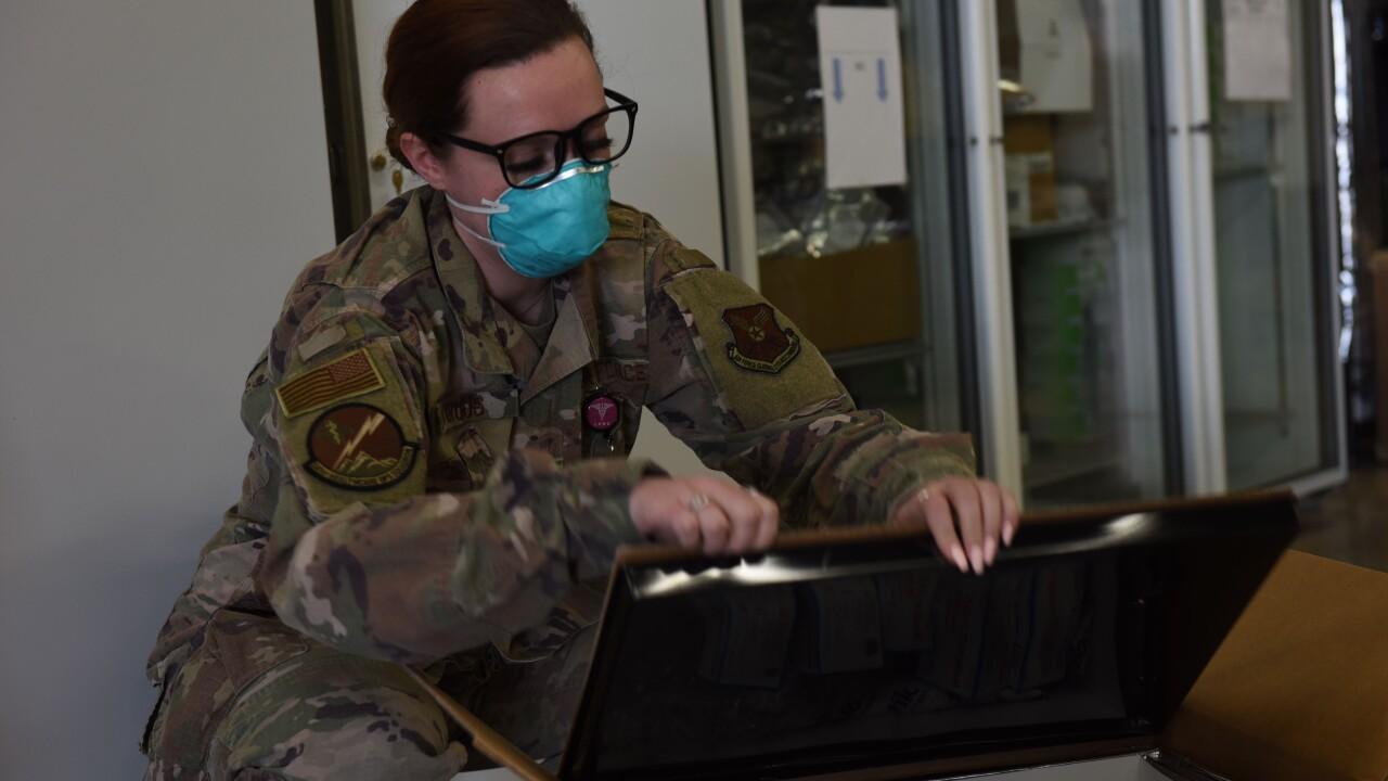 Staff Sgt. Michelle Krous, 341st Healthcare Operations Squadron NCO in charge of acquisitions, opens a box of COVID-19 vaccines