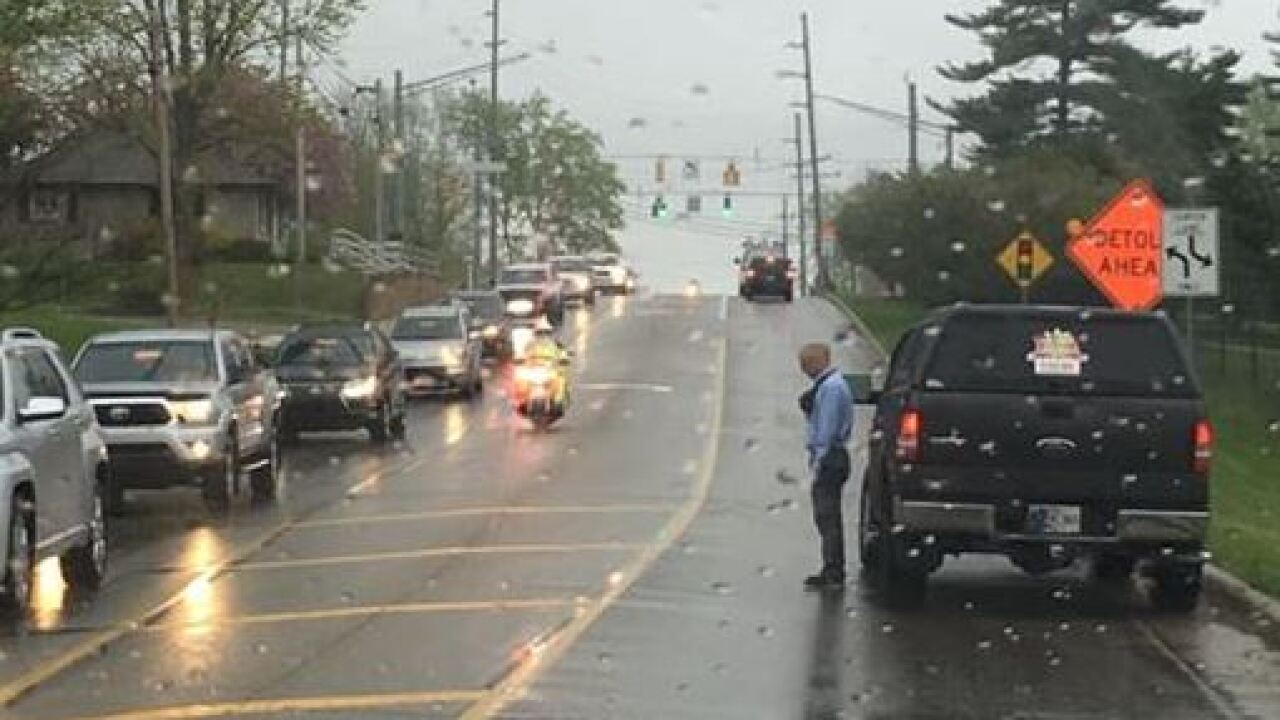 Photo of man standing at the side of the road, in the rain, during funeral procession goes viral