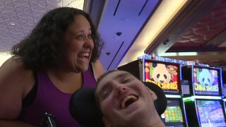 Stephanie Johnstone-Wagner pushes Ethan Kadish in his wheelchair past slot machines at Hard Rock Casino Cincinnati. They are both smiling broadly in the photo.