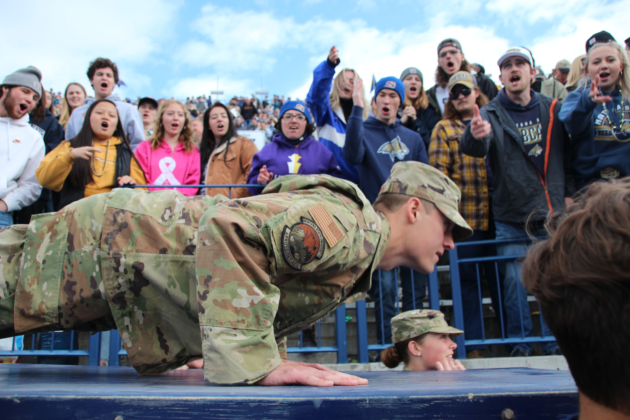 A soldier does push ups as fans look on after a MSU TD