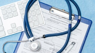 Stethoscope laying over doctors emergency report