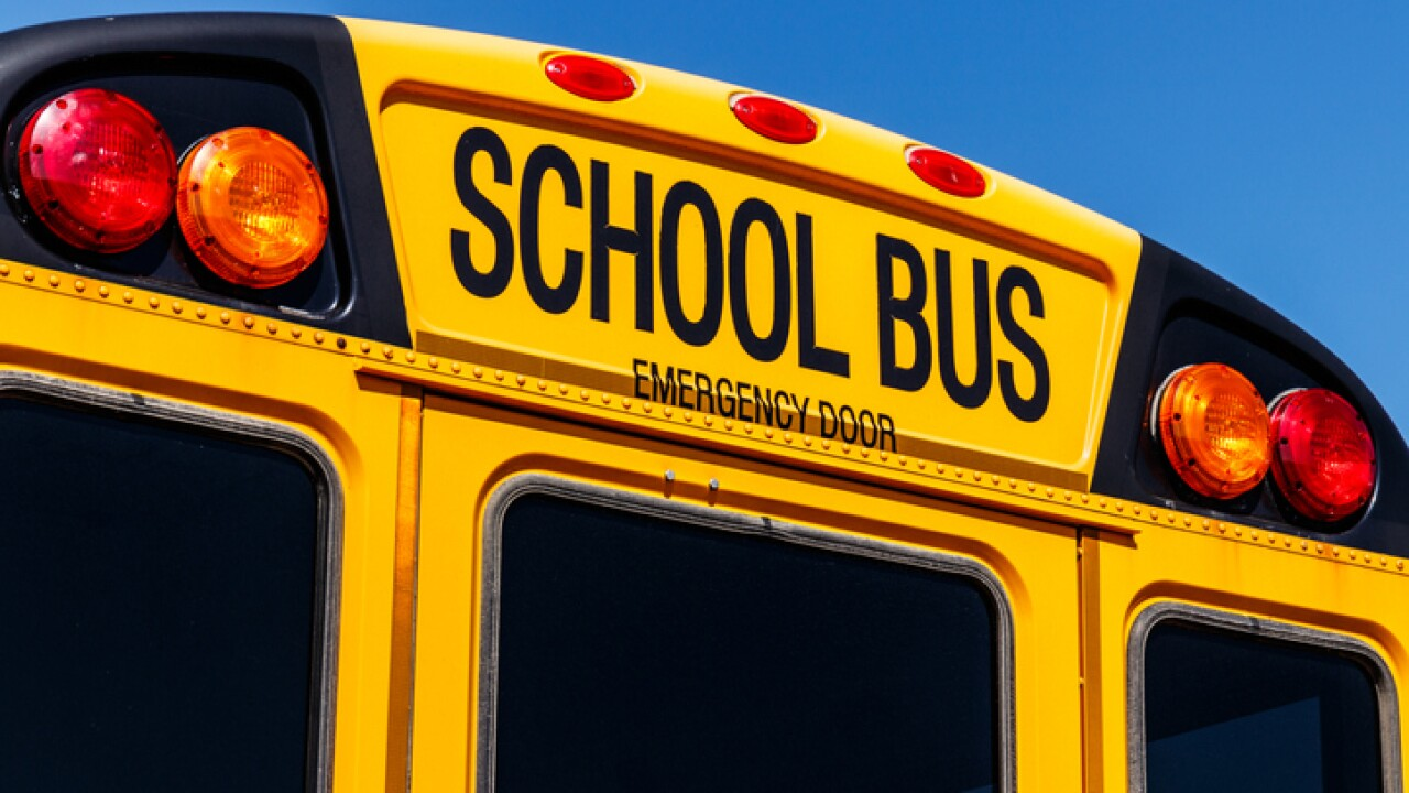 Students exit school bus through emergency door after driver stops to discuss behavior