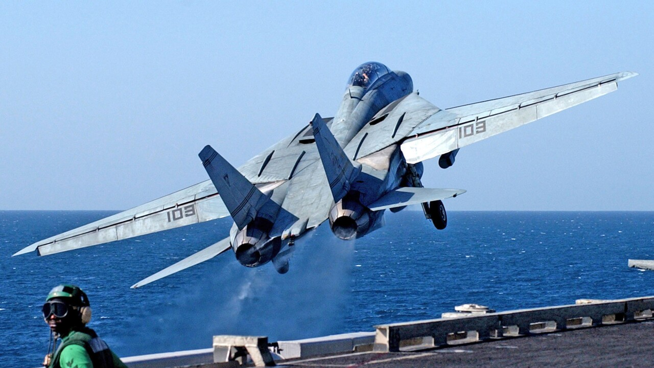 Off the waist catapults, launches an F-14B Tomcat