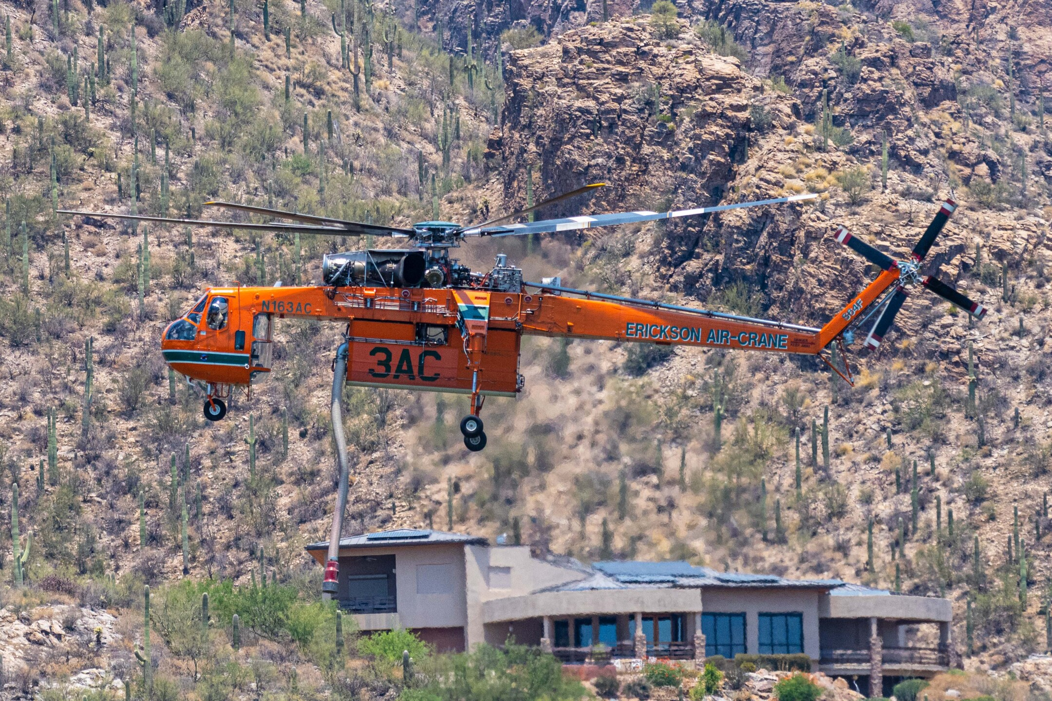 A chopper pilot dips into Ventana Pond to scoop up water while fighting the Bighorn Fire in the Catalina Mountains