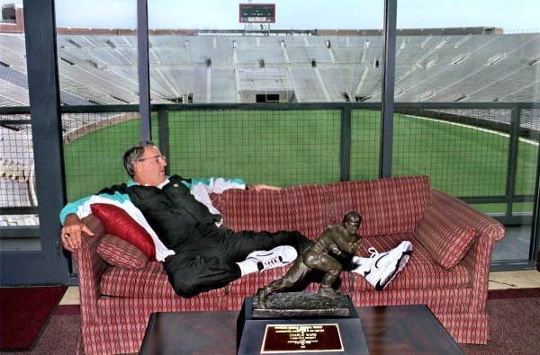 Florida State Seminoles head coach Bobby Bowden lounges with Charlie Ward's Heisman Trophy
