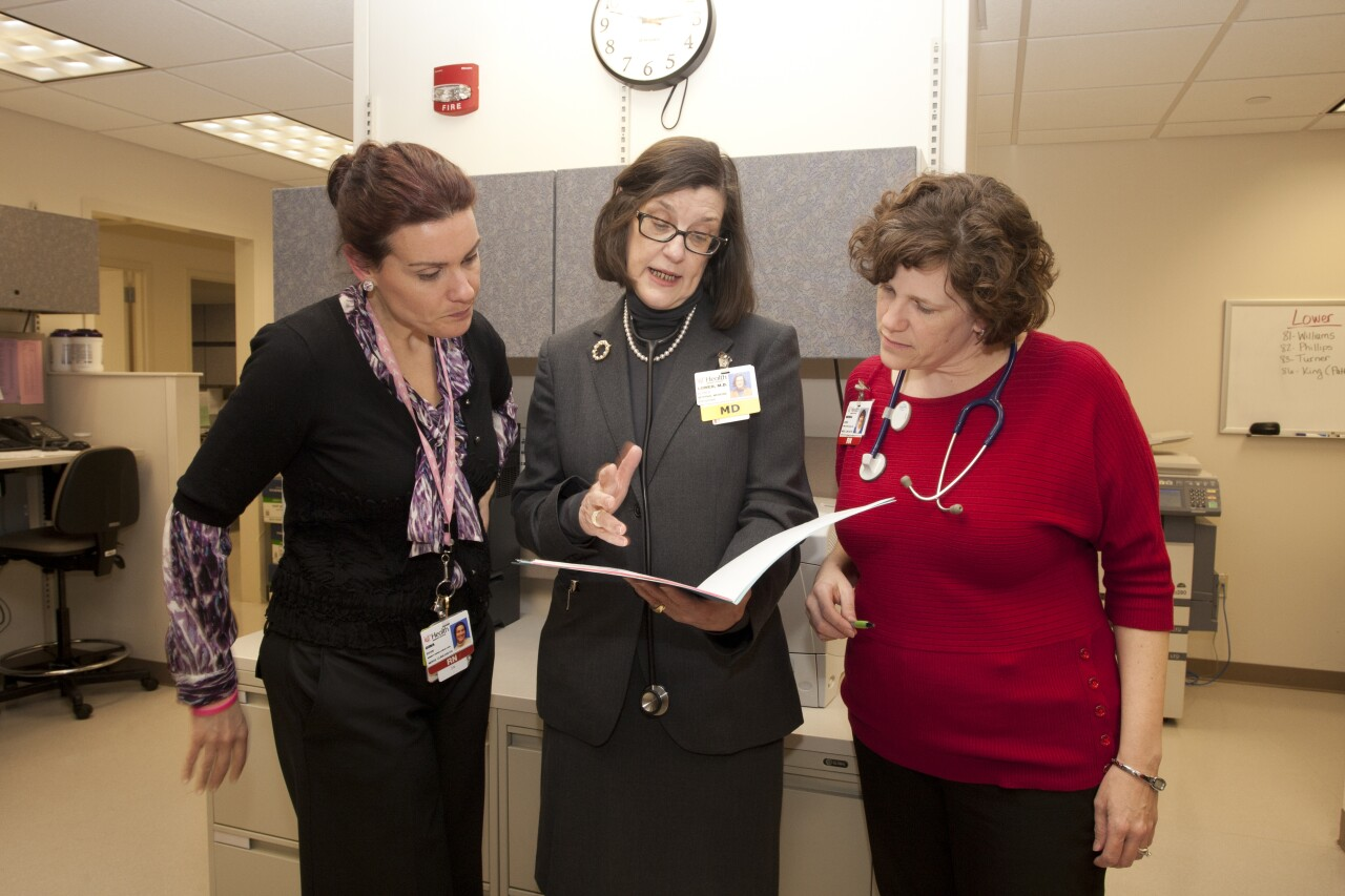 Dr. Elyse Lower, center, talks with colleagues at UC Health. Lower is holding a file, and two people are standing on either side of her.
