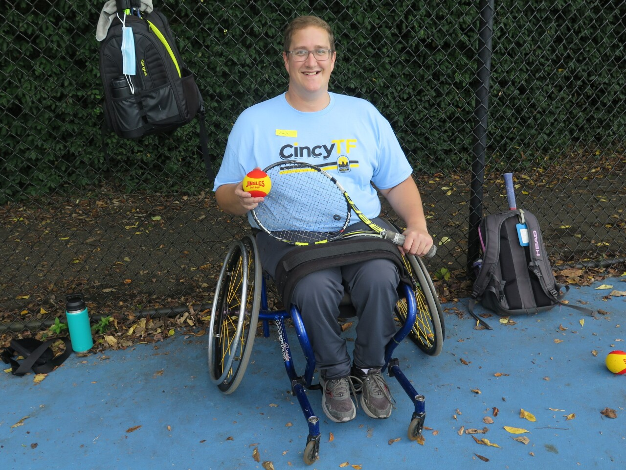 Zack Sikora is smiling and holding a tennis ball and tennis racquet in this photo. He's wearing glasses, a blue Cincinnati Tennis Foundation t-shirt and dark trousers, and he's seated in a wheelchair.