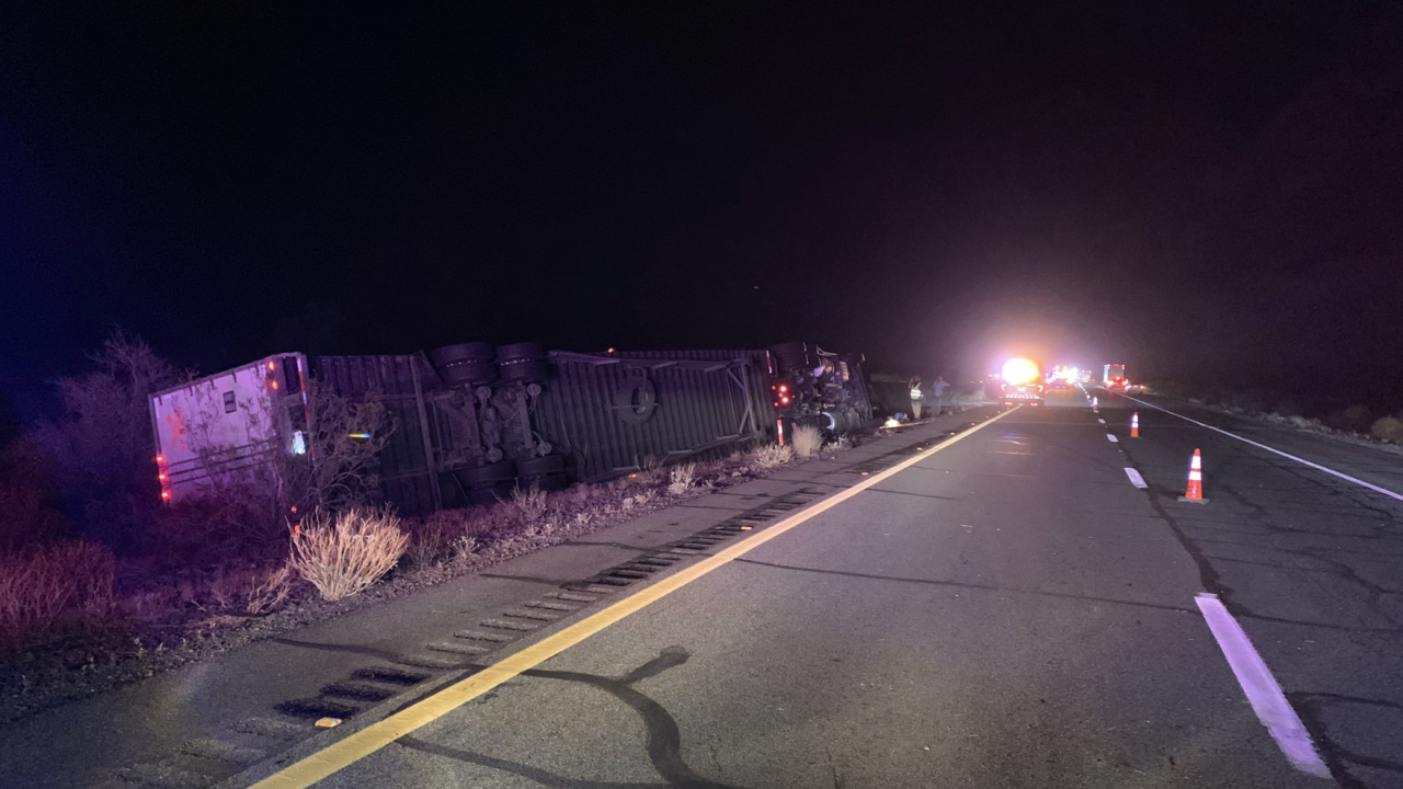 Authorities say strong winds during a rainstorm blew over six big rigs in multiple wrecks on Interstate 10 in southwestern Arizona, killing one person and injuring another.