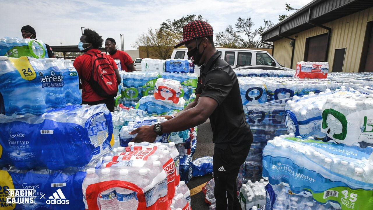 Levi Lewis helps carry water in Hurricane Laura relief delivery