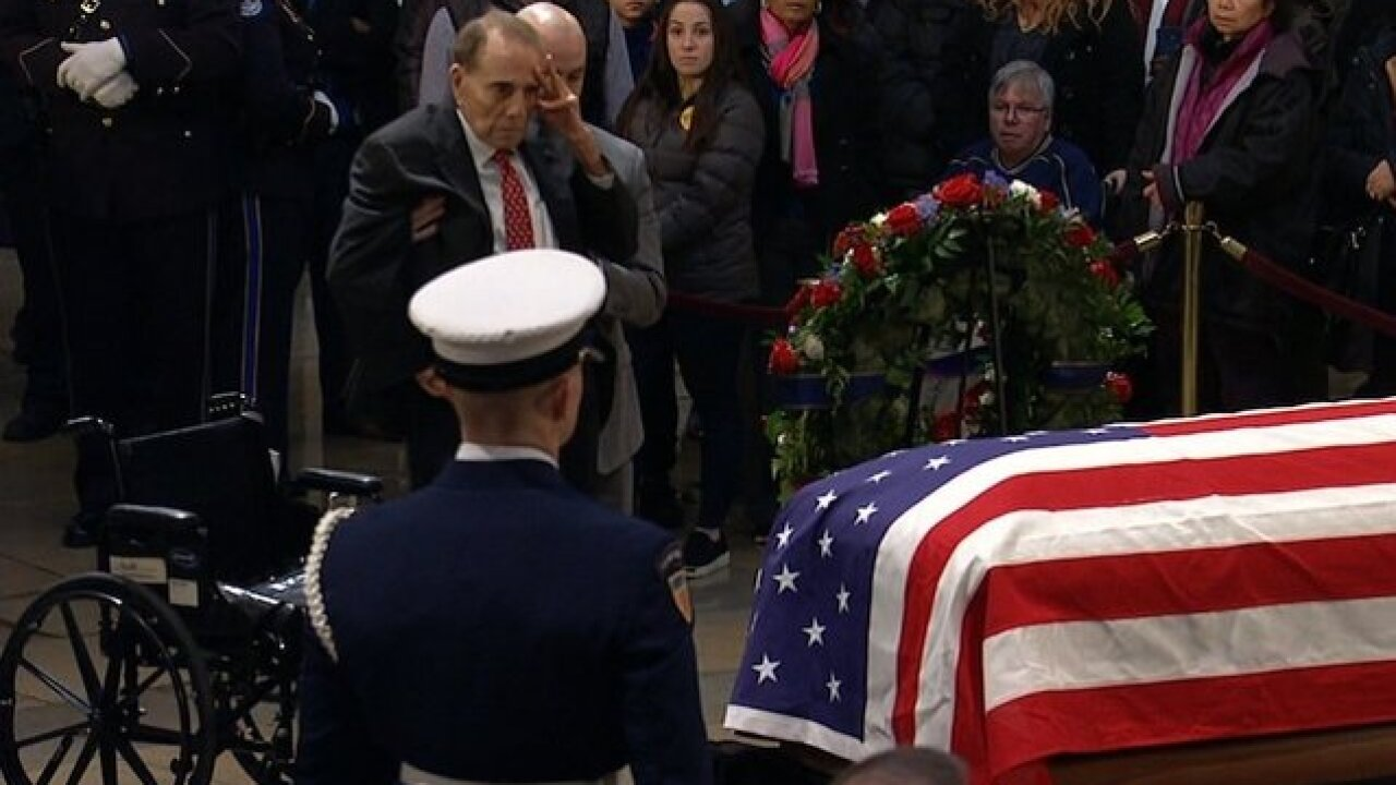 Watch: Bob Dole helped out of his wheelchair to salute George H.W. Bush