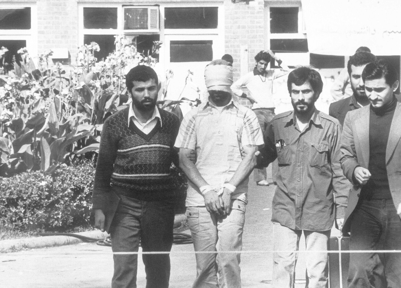 In this Nov. 8, 1979 file photo, one of the hostages held at the U.S. Embassy in Tehran, Iran is shown to the crowd by Iranian students. The 444-day hostage crisis that soured relations between the U.S. and the Islamic Republic for decades to come. (AP Photo, File)