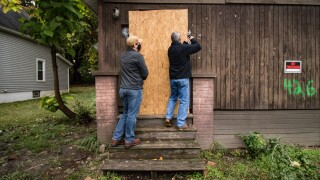 Summit County Land Bank program director Jim Davis and staff attorney Drew Reilly secure a plywood over the front door at 426 McGowan St. (H.L. Comeriato).jpg