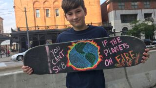 Boy with skateboard at climate change protest in Milwaukee