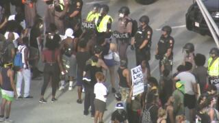 Protesters, including one holding 'black lives matter' sign, confront police on I-95