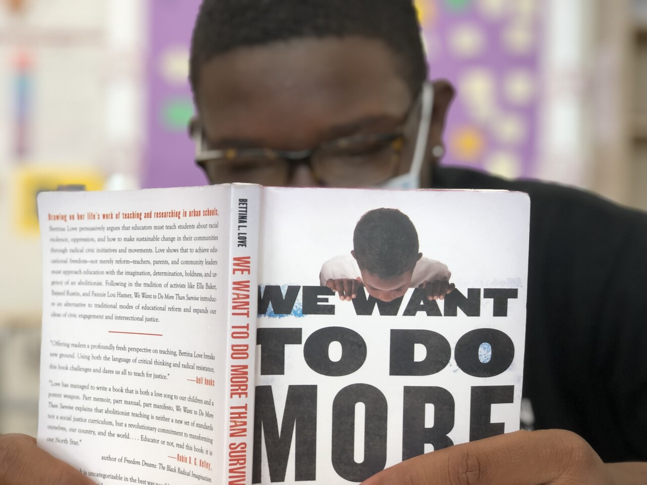 """An Aiken High School student reads in preparation for a discussion with Keith Lamar, a death row inmate at the Ohio State Penitentiary. The student is wearing glasses and a mask and is reading """"We Want to Do More Than Survive"""" by Bettina Love."""