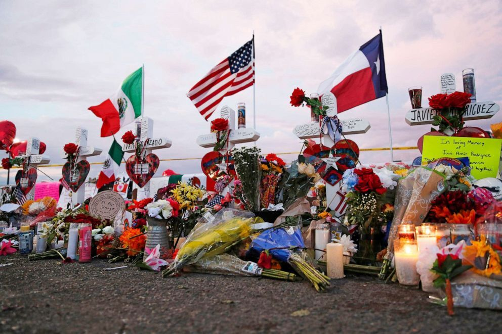 Flags fly over crosses at a makeshift memorial near the scene of a mass shooting at a shopping complex Tuesday, Aug. 6, 2019, in El Paso, Texas.