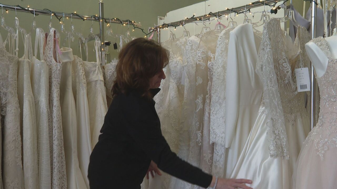 Chris Salazar, co-owner of Bella Sposa Bridal Boutique, stands next to a rack of wedding gowns.