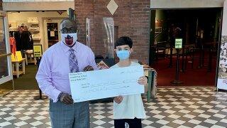 Riordan Nash, 13, presents $520 check to the Negro Leagues Baseball Museum