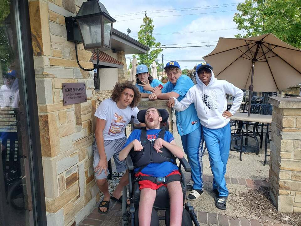 This photo shows Ethan Kadish in his wheelchair posing with friends after attending a baseball tournament in July 2021.