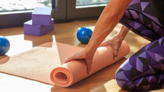 Woman rolling a yoga mat on wooden floor