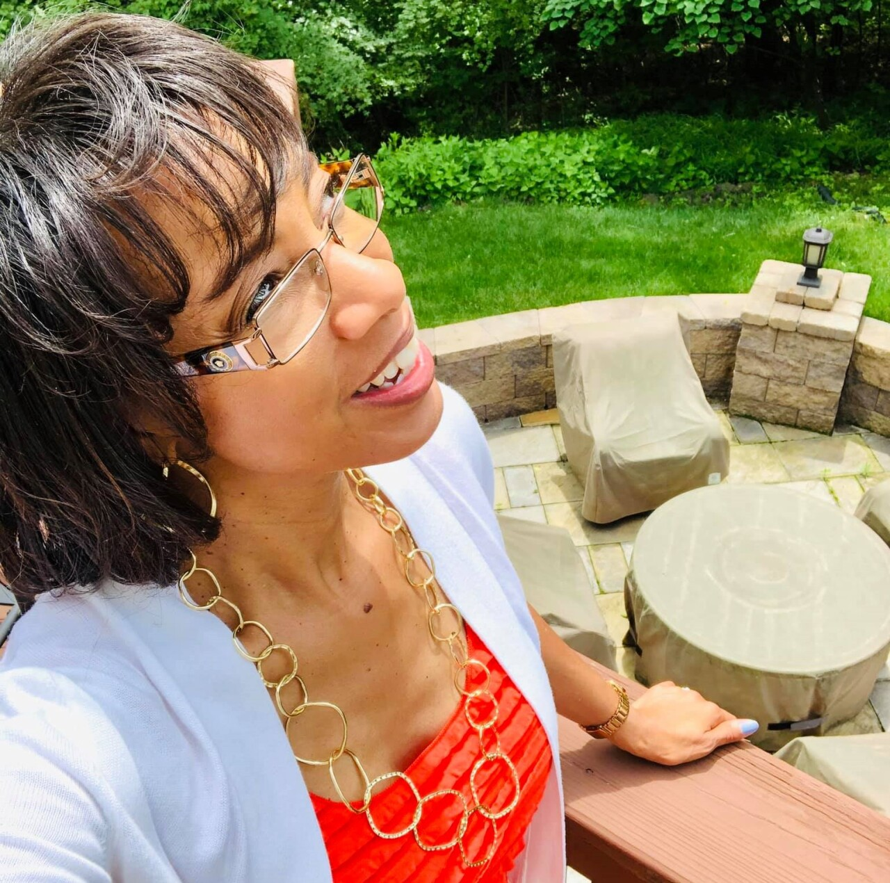 Sherry Hughes in a photo dated June 23, 2019, about a month before her breast cancer diagnosis. She is looking up into the sky and holding onto the railing of her back deck.