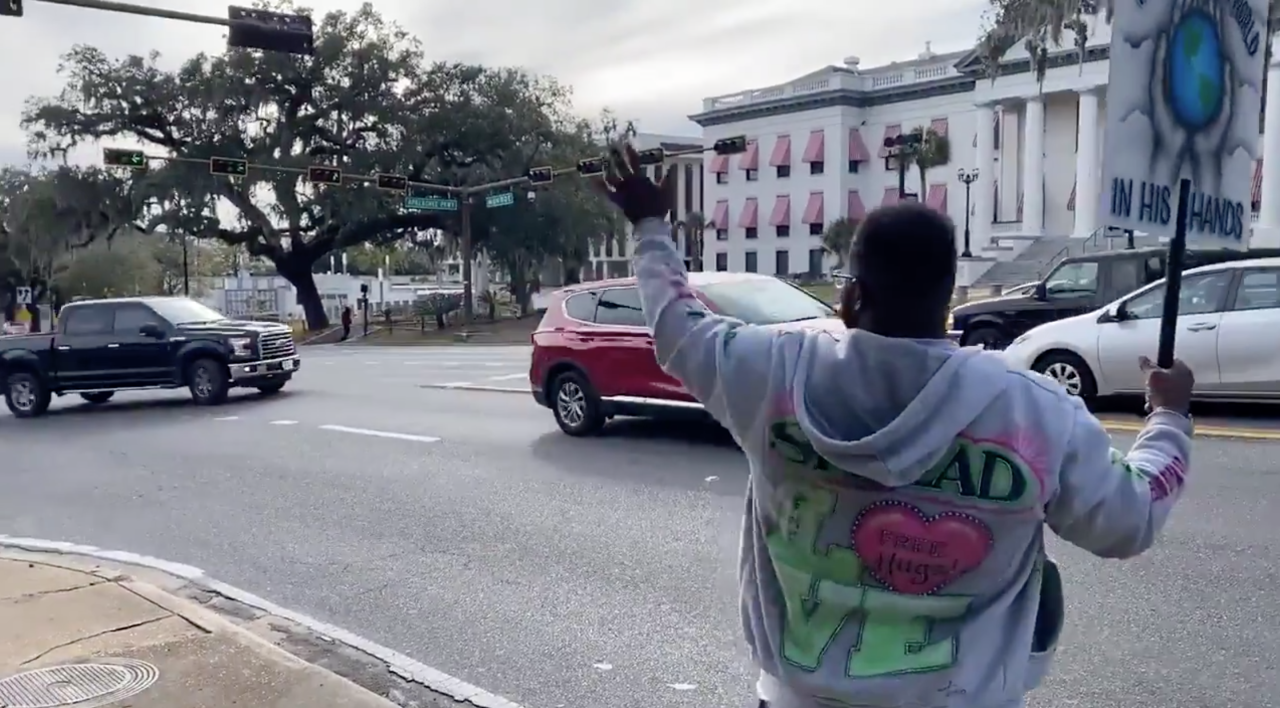 Person waves to passersby at Florida Capitol