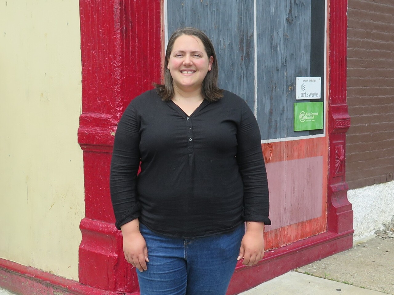 Mary Delaney poses for a photo outside one of the buildings that will be renovated as part of LPH Thrives. This photo was taken in June 2020. Delaney is wearing a black long-sleeved top and jeans and has shoulder-length brown hair.