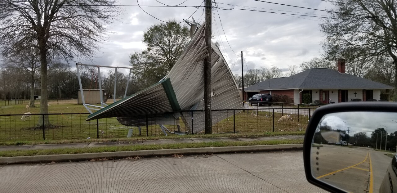 Winds blew a carport roof into a fence.