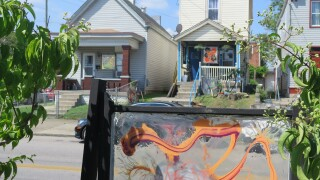 A window painted with an abstract, orange design is the foreground of this photo. Two homes on Russell Street in Covington, Ky., are in the background. Both homes also are displaying painted windows.