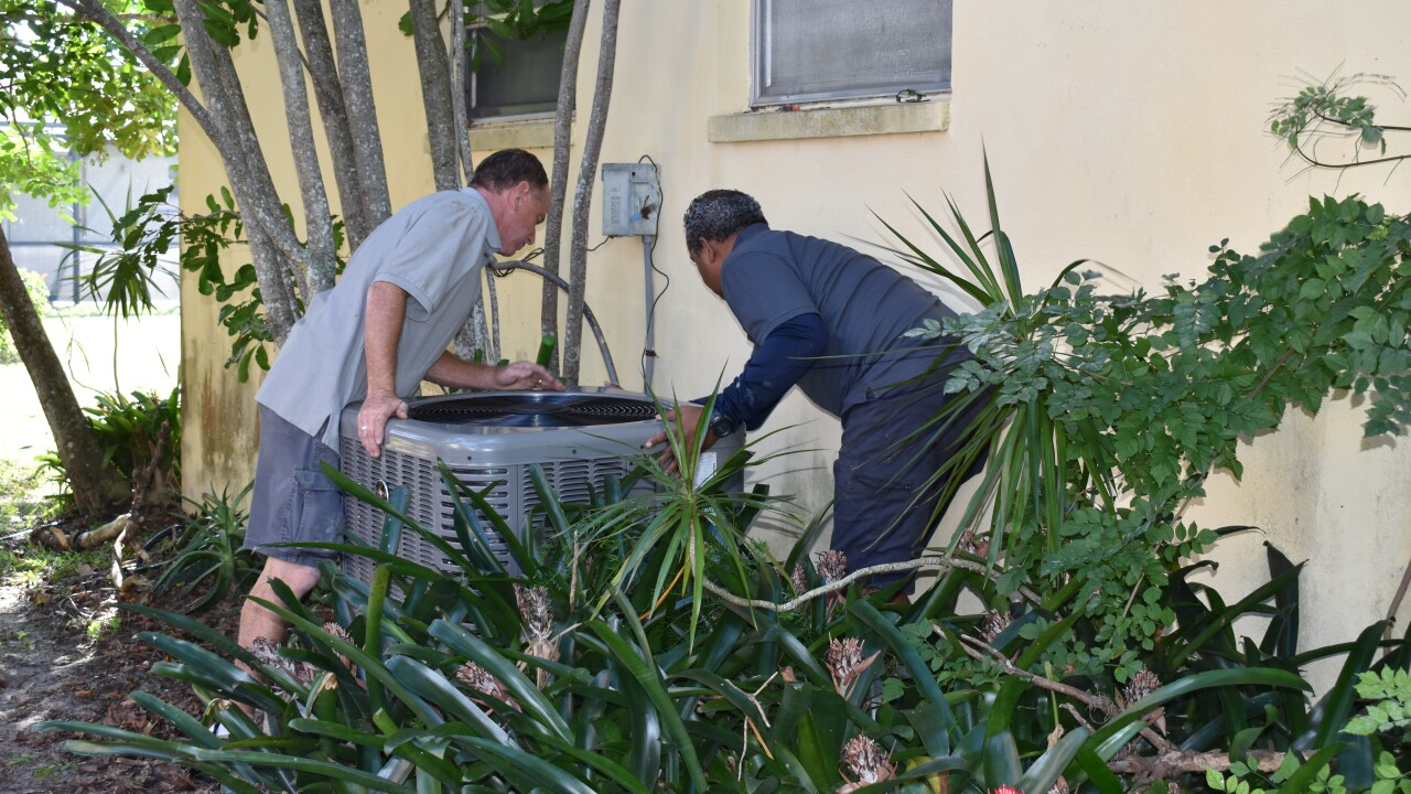 Photo 6 - Volunteers install AC unit at the home of Jon Smith.JPG