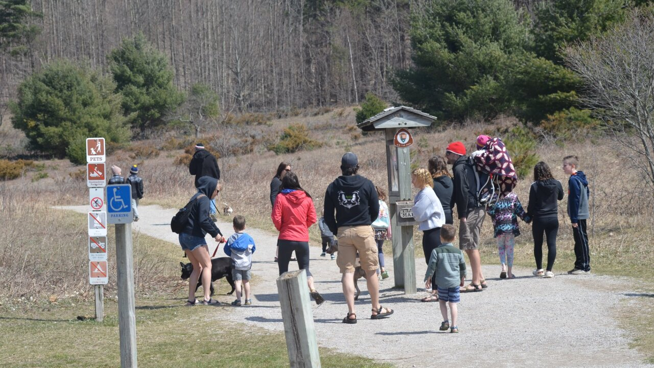 People crowd around wooden sign at Sleeping Bear Dunes