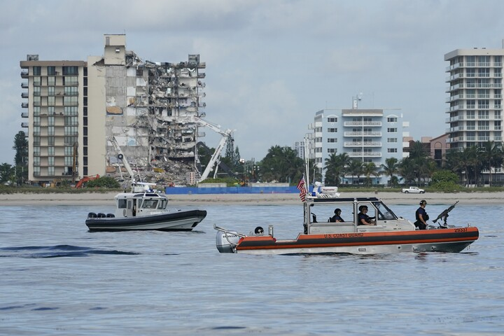 A Coast Guard boat patrols alongside a Miami-Dade County police boat, in front of the partially collapsed Champlain Towers South condo building, ahead of a planned visit to the site by President Joe Biden, on Thursday, July 1, 2021, in Surfside, Fla.jpg