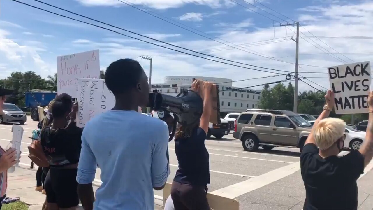 A group of protesters gathers at the intersection of Forest Hill Boulevard and Highway 441 in Wellington on Monday, June 8, 2020.