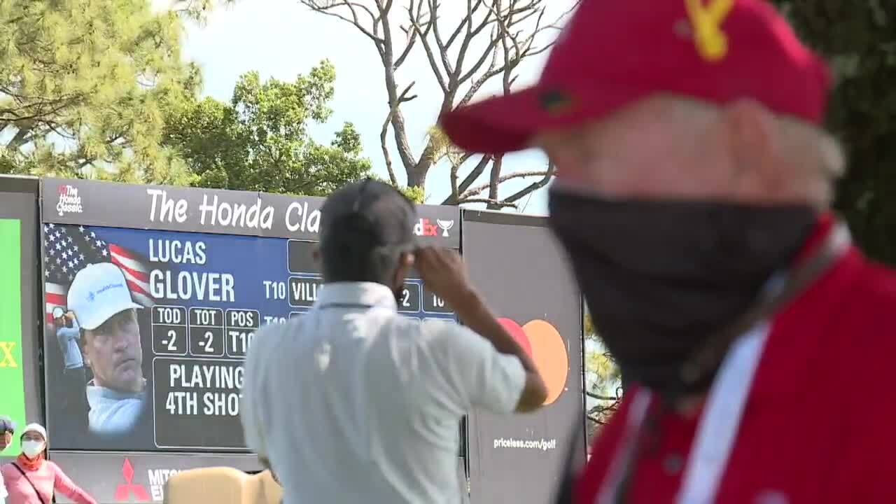 Electronic billboard for Lucas Glover on display at 2021 Honda Classic as Tom Gibbs waits in shade