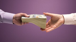 Man and woman's hands handing pile of cash