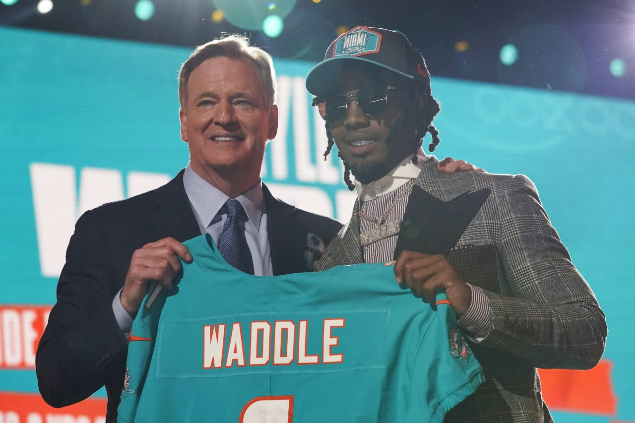 Jaylen Waddle and NFL Commissioner Roger Goodell hold Miami Dolphins jersey during first round of 2021 NFL Draft
