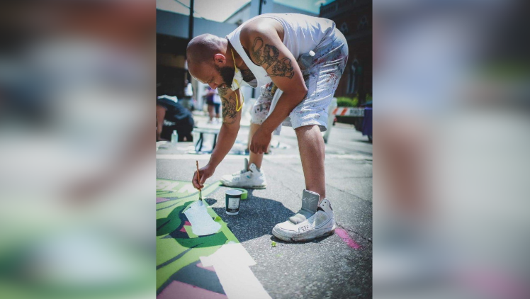 Brandon Hawkins painting the B in the Black Lives Matter mural