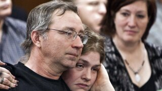"""FILE - In this Thursday, Feb. 19, 2009, file photo, Joseph White, left, one of six people wrongly convicted of the rape and murder of Helen Wilson in 1985, is hugged by Rachel Morgan, daughter of Ada Joann Taylor, another member of the """"Beatrice Six,"""" right, following his testimony before the Judiciary Committee in Lincoln, Neb. A Nebraska county that owes more than $30 million to six people wrongfully convicted of murder has approved a new half-cent sales tax to help pay the legal judgment, but the former prisoners will still have to wait at least six years to collect the full amount they're owed. (AP Photo/Nati Harnik, File)"""