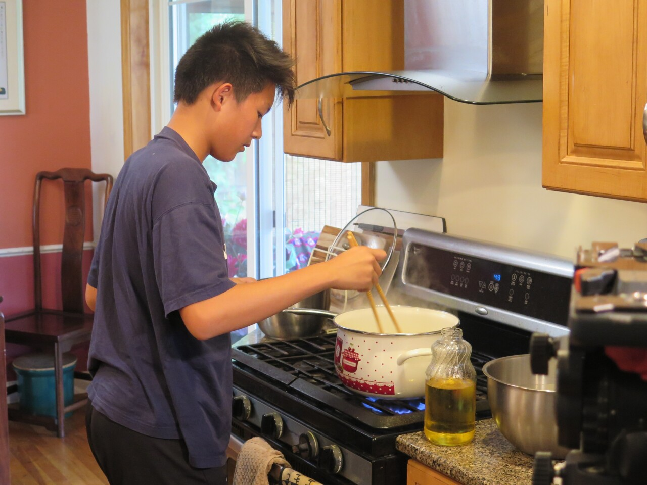 Edward Zha cooking noodles for Biang Biang Mian. He is wearing a dark blue t-shirt and is using chop sticks to stir a pot of noodles.