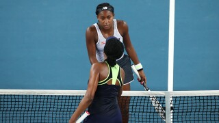 Coco Gauff of the United States of America and Venus Williams of the United States of America embrace at the net following their Women's Singles first round match on day one of the 2020 Australian Open at Melbourne Park on January 20, 2020 in Melbourne, Australia.