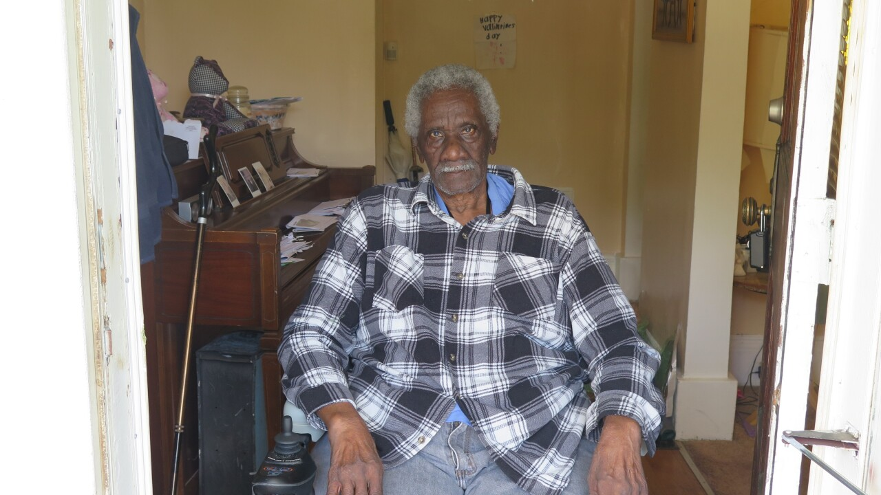Robert McCrary poses inside the entryway of his Avondale home. He has grey hair and a grey mustache and is wearing a black and white plaid shirt.